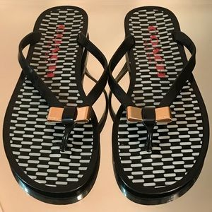 COACH black flip flops with gold bow.